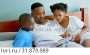 Купить «Front view of mid adult black father with his children reading story book in bedroom of comfortable », видеоролик № 31879989, снято 7 ноября 2018 г. (c) Wavebreak Media / Фотобанк Лори
