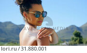 Купить «Side view of young mixed-race woman applying sunscreen on her shoulder near swimming pool 4k», видеоролик № 31880001, снято 7 ноября 2018 г. (c) Wavebreak Media / Фотобанк Лори
