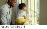 Купить «Side view of young black father playing with his son on window sill in a comfortable home 4k», видеоролик № 31880013, снято 19 октября 2018 г. (c) Wavebreak Media / Фотобанк Лори