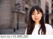 Купить «Portrait of cheerful young chinese longhaired woman standing on a city street», фото № 31880281, снято 19 августа 2019 г. (c) Яков Филимонов / Фотобанк Лори