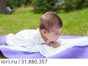 Купить «Newborn infant one month old lying on white bedsheet on lawn and first time holds head straight», фото № 31880357, снято 17 июля 2019 г. (c) Кекяляйнен Андрей / Фотобанк Лори