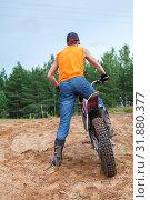 Купить «Riding motorcross motorcycle in sandy pit, Caucasian man dressed orange t-shirt standing with bike, rear view», фото № 31880377, снято 20 июля 2019 г. (c) Кекяляйнен Андрей / Фотобанк Лори