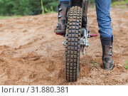 Купить «Motorcycle racer with boots standing on peg of dirt bike on sandy track», фото № 31880381, снято 20 июля 2019 г. (c) Кекяляйнен Андрей / Фотобанк Лори
