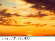 Купить «Beautiful bright majestic dramatic evening sky at sunset orange color with rays. The sun shines over the horizon against the backdrop of thunderclouds at dusk», фото № 31880433, снято 28 июня 2019 г. (c) Светлана Евграфова / Фотобанк Лори