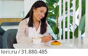 Купить «asian woman with notebook and coffee at cafe», видеоролик № 31880485, снято 21 июля 2019 г. (c) Syda Productions / Фотобанк Лори