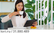 Купить «asian woman with tablet pc at cafe or coffee shop», видеоролик № 31880489, снято 21 июля 2019 г. (c) Syda Productions / Фотобанк Лори