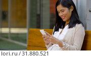 Купить «asian woman using smartphone sitting on bench», видеоролик № 31880521, снято 21 июля 2019 г. (c) Syda Productions / Фотобанк Лори