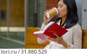 Купить «smiling asian woman reading book sitting on bench», видеоролик № 31880529, снято 21 июля 2019 г. (c) Syda Productions / Фотобанк Лори