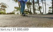 Купить «Front view of young male skateboarder riding on skateboard on country road 4k», видеоролик № 31880689, снято 16 октября 2018 г. (c) Wavebreak Media / Фотобанк Лори