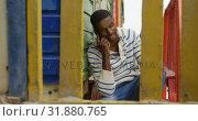Купить «Front view of young black man talking on mobile phone sitting on stairs of hut at beach 4k», видеоролик № 31880765, снято 14 ноября 2018 г. (c) Wavebreak Media / Фотобанк Лори
