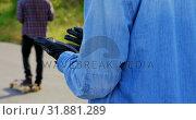 Купить «Side view of young caucasian male skateboarder looking at his skateboard gloves on country road 4k», видеоролик № 31881289, снято 16 октября 2018 г. (c) Wavebreak Media / Фотобанк Лори