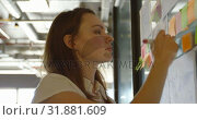 Купить «Front view of young caucasian businesswoman using digital tablet and working on glass wall 4k», видеоролик № 31881609, снято 13 октября 2018 г. (c) Wavebreak Media / Фотобанк Лори