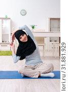 Купить «Young woman in hijab doing exercises at home», фото № 31881929, снято 18 марта 2019 г. (c) Elnur / Фотобанк Лори