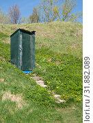 Купить «Деревянная старая туалетная кабинка, обшитая мелкой темно-зеленой сеткой, на поросшем свежей зеленой травой склоне и ступеньки, ведущие к ней», фото № 31882089, снято 5 мая 2019 г. (c) Наталья Николаева / Фотобанк Лори