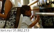 Side view of cute little black son looking in colander in kitchen of comfortable home 4k. Стоковое видео, агентство Wavebreak Media / Фотобанк Лори