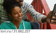 Купить «Front view of young black couple clicking selfie with mobile phone while sitting on stairs of hut 4k», видеоролик № 31882257, снято 14 ноября 2018 г. (c) Wavebreak Media / Фотобанк Лори