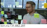 Купить «Male executive writing on glass wall in office 4k», видеоролик № 31882281, снято 16 июня 2018 г. (c) Wavebreak Media / Фотобанк Лори