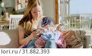 Купить «Front view of mid adult caucasian mother feeding milk her baby from bottle in a comfortable home 4k», видеоролик № 31882393, снято 22 июня 2018 г. (c) Wavebreak Media / Фотобанк Лори