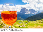View of the traditional Italian alcoholic drink Aperol Spritz on the background of colorful Italian meadows and the Dolomites Alps mountains. village St. Cristina di Val Gardena Bolzano Seceda, Italy. Стоковое фото, фотограф Алексей Ширманов / Фотобанк Лори