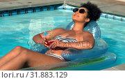 Woman relaxing on floating pool lounger in swimming pool 4k. Стоковое видео, агентство Wavebreak Media / Фотобанк Лори