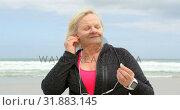 Купить «Front view of old caucasian senior woman listening music on earphones at beach 4k», видеоролик № 31883145, снято 6 ноября 2018 г. (c) Wavebreak Media / Фотобанк Лори