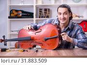 Купить «Young handsome repairman repairing cello», фото № 31883509, снято 4 апреля 2019 г. (c) Elnur / Фотобанк Лори