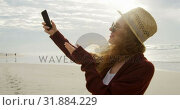 Купить «Side view of young beautiful caucasian woman clicking selfie with mobile phone at beach 4k», видеоролик № 31884229, снято 14 ноября 2018 г. (c) Wavebreak Media / Фотобанк Лори