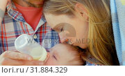 Купить «Close-up of mid adult caucasian parents feeding their baby from a bottle on a sunny day 4k», видеоролик № 31884329, снято 22 июня 2018 г. (c) Wavebreak Media / Фотобанк Лори