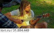 Купить «Man playing guitar at camp in the forest 4k», видеоролик № 31884449, снято 12 октября 2018 г. (c) Wavebreak Media / Фотобанк Лори