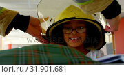 Купить «Firefighter helping African American schoolgirl by putting helmet on her head in classroom at school», видеоролик № 31901681, снято 10 ноября 2018 г. (c) Wavebreak Media / Фотобанк Лори
