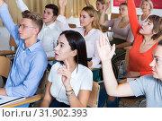 Купить «People in classroom raising hands to answer», фото № 31902393, снято 22 сентября 2019 г. (c) Яков Филимонов / Фотобанк Лори