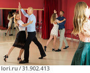 Купить «Positive adult couples dancing tango together in modern studio», фото № 31902413, снято 4 октября 2018 г. (c) Яков Филимонов / Фотобанк Лори
