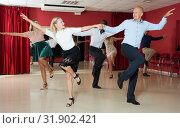 Young positive people dancing twist in pairs at dance hall together. Стоковое фото, фотограф Яков Филимонов / Фотобанк Лори