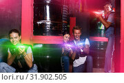 Купить «Smiling friends playing laser tag game with laser guns in lab», фото № 31902505, снято 23 августа 2018 г. (c) Яков Филимонов / Фотобанк Лори