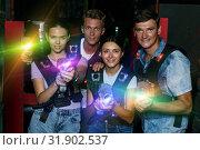 Купить «Group of smiling young friends holding laser guns during laser t», фото № 31902537, снято 23 августа 2018 г. (c) Яков Филимонов / Фотобанк Лори