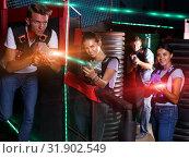 Купить «Young men and girl in waistcoats with laser guns playing laser t», фото № 31902549, снято 23 августа 2018 г. (c) Яков Филимонов / Фотобанк Лори