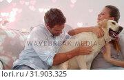 Купить «Couple playing with a dog on the couch against illustration of hearts», видеоролик № 31903325, снято 16 января 2019 г. (c) Wavebreak Media / Фотобанк Лори