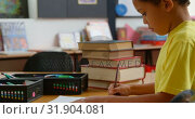Купить «Side view of African American schoolboy studying at desk in classroom at school 4k», видеоролик № 31904081, снято 17 ноября 2018 г. (c) Wavebreak Media / Фотобанк Лори