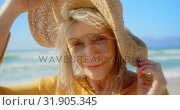 Купить «Front view of active senior Caucasian woman in hat standing on the beach 4k», видеоролик № 31905345, снято 14 ноября 2018 г. (c) Wavebreak Media / Фотобанк Лори