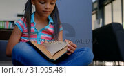 Купить «Front view of attentive African American schoolgirl reading a book in library at school 4k», видеоролик № 31905481, снято 17 ноября 2018 г. (c) Wavebreak Media / Фотобанк Лори