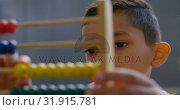 Купить «Front view of Asian schoolboy solving math problem with abacus at desk in a classroom at school 4k», видеоролик № 31915781, снято 17 ноября 2018 г. (c) Wavebreak Media / Фотобанк Лори