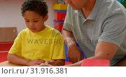 Купить «Front view of young Caucasian male teacher teaching African American schoolboy in classroom 4k», видеоролик № 31916381, снято 17 ноября 2018 г. (c) Wavebreak Media / Фотобанк Лори