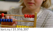 Front view of Caucasian schoolgirl learning mathematics with abacus in the classroom 4k. Стоковое видео, агентство Wavebreak Media / Фотобанк Лори
