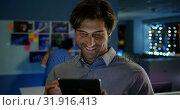 Купить «Front view of happy young Caucasian male executive working on digital tablet in modern office 4k», видеоролик № 31916413, снято 29 ноября 2018 г. (c) Wavebreak Media / Фотобанк Лори