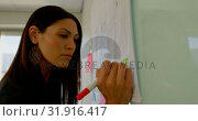 Купить «Side view of young Caucasian female executive with digital tablet working on glass board 4k», видеоролик № 31916417, снято 29 ноября 2018 г. (c) Wavebreak Media / Фотобанк Лори