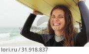 Front view of Caucasian female surfer carrying surfboard on her head at beach 4k. Стоковое видео, агентство Wavebreak Media / Фотобанк Лори
