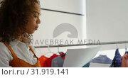 Купить «Side view of African American female fashion designer holding sketch sheet in workshop 4k», видеоролик № 31919141, снято 18 ноября 2018 г. (c) Wavebreak Media / Фотобанк Лори