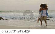 Купить «African american man giving piggyback ride to woman on the beach 4k», видеоролик № 31919429, снято 12 ноября 2018 г. (c) Wavebreak Media / Фотобанк Лори