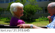 Side view of active Caucasian senior couple interacting with each other in the garden of nursing hom. Стоковое видео, агентство Wavebreak Media / Фотобанк Лори