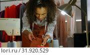 Купить «Front view of African American female fashion designer looking at cloth samples in workshop 4k», видеоролик № 31920529, снято 18 ноября 2018 г. (c) Wavebreak Media / Фотобанк Лори
